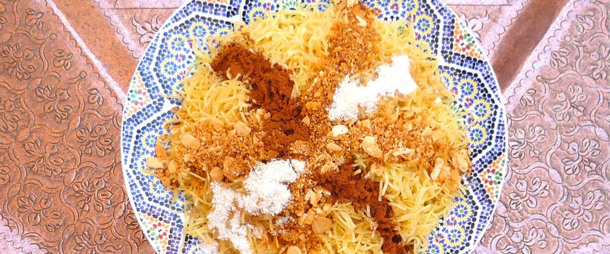 photo of plate of moroccan seffa pasta crossed with powdered cinnamon, sugar, almonds of 1 meter wide engraved copper moroccan plate