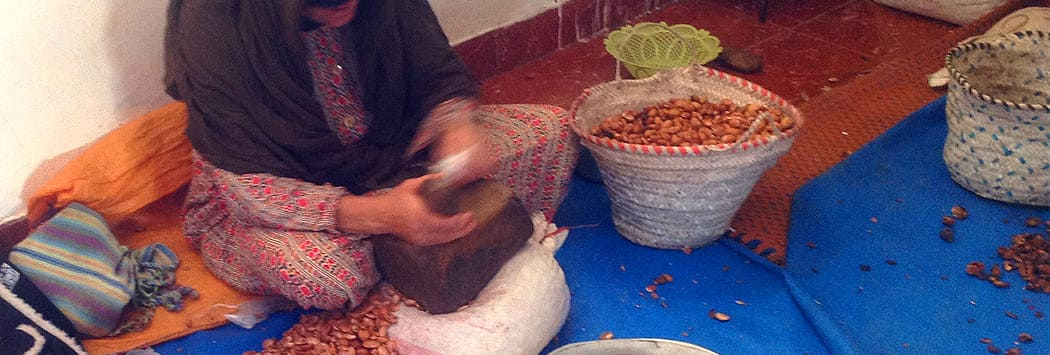 Berber women using stone to crack open hard argan nuts