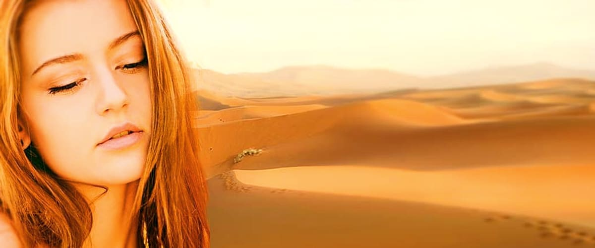 woman with red hair in front of sand dunes